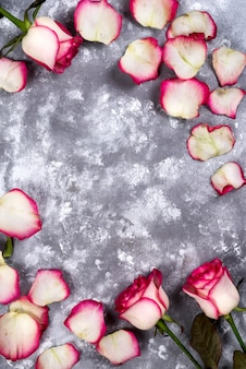 Marco floral: ramo de rosas blancas rosas sobre fondo de piedra