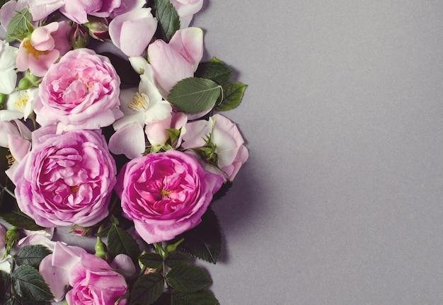 Marco floral. rosa flores sobre un fondo gris. lay flat