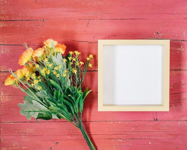 Marco con flores amarillas sobre fondo de madera rosa