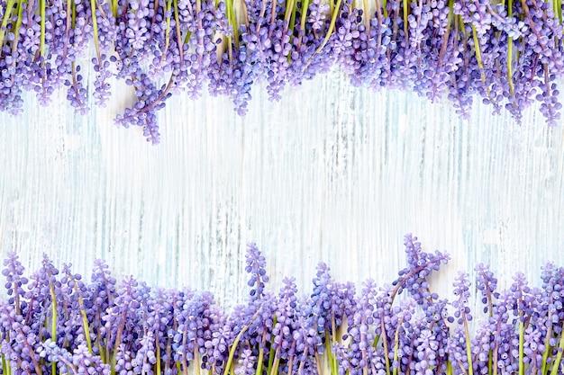 Marco de flores azules muscari en madera azul