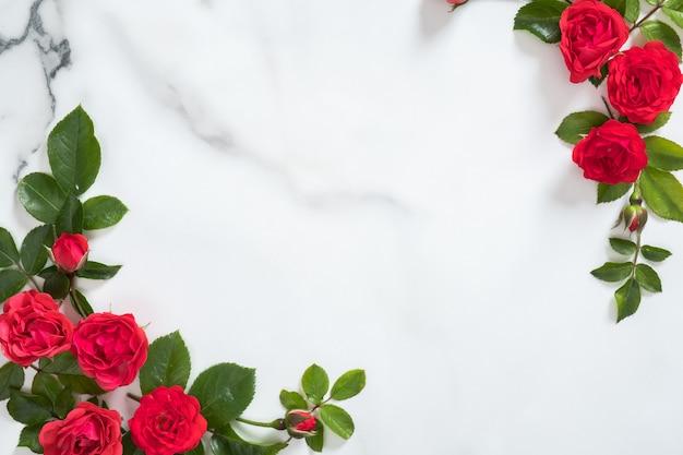 Marco de flores con capullos de rosas y hojas verdes sobre fondo de mármol