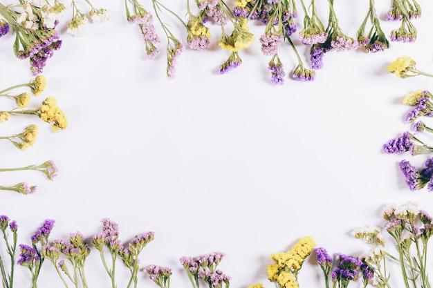 Marco de flores de colores sobre un fondo blanco
