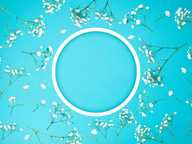 Marco de flores creativo hecho de flores decorativas blancas con círculo y espacio de copia