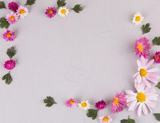 Marco de flores y hojas en mesa.