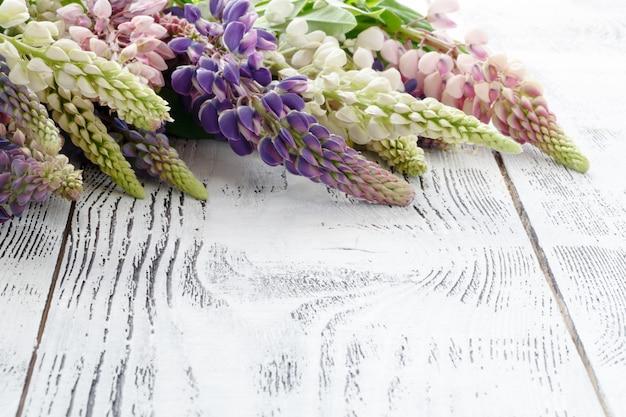 Marco de flores de lupino un viejo fondo pintado de madera
