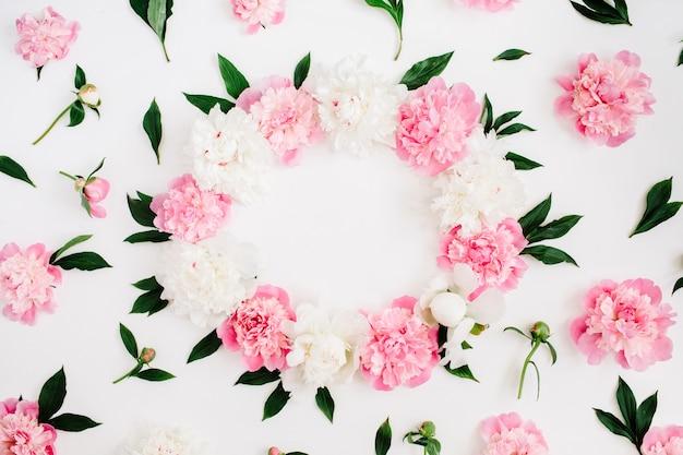 Marco de flores de peonía rosa, ramas, hojas y pétalos en blanco