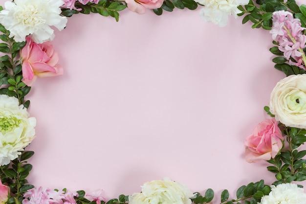 Marco de flores con ramas frescas de rosas en forma de pión y hojas de eucalipto aisladas sobre fondo blanco, plano y vista superior