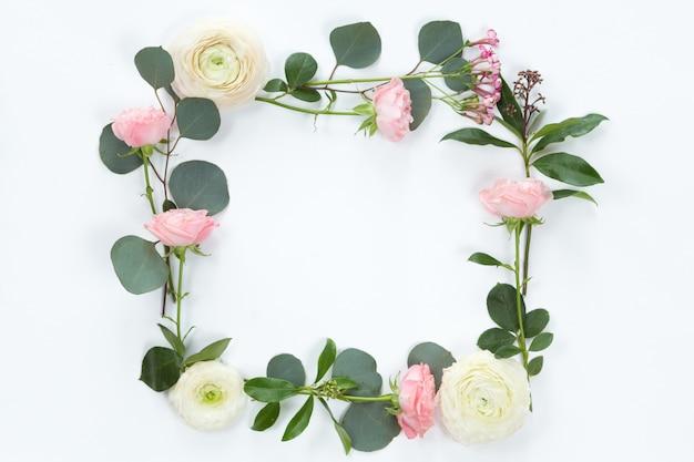 Marco de flores con ramas frescas de rosas en forma de pion y hojas de eucalipto