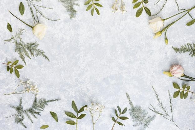 Marco de flores rosas y ramas de plantas en mesa