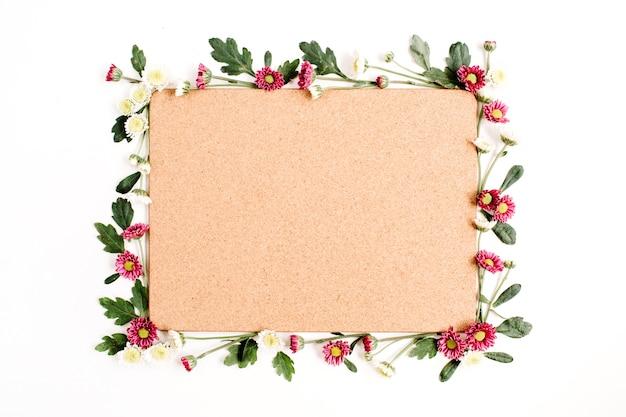 Marco con flores silvestres rojas y blancas, hojas verdes, ramas y tablero de árbol de corcho de madera sobre superficie blanca