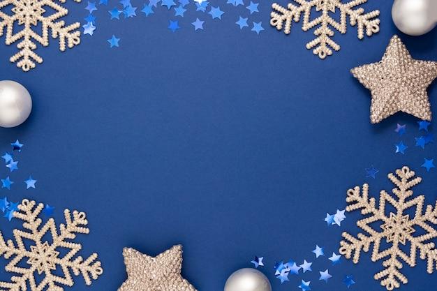 Marco de fondo abstracto azul de navidad con copos de nieve de plata, adornos y decoración de invierno de confeti, maqueta azul con espacio para texto.