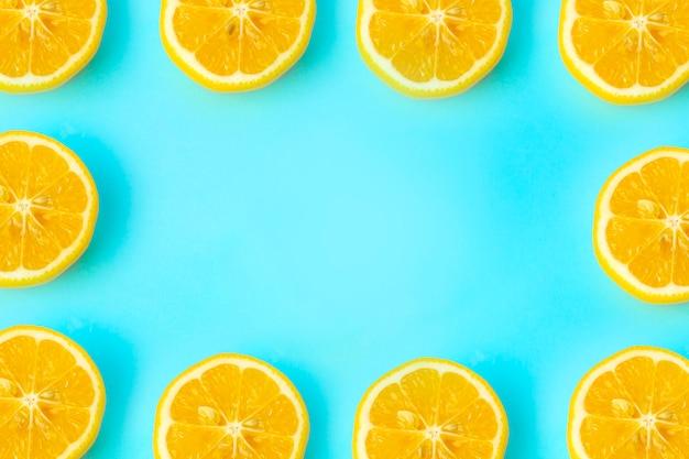 Marco de fondo de verano y vitaminas. limón sobre un fondo azul, concepto de comida mínima