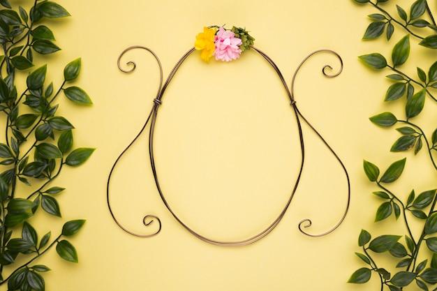 Marco de forma ovalada con rosa artificial en pared amarilla con hojas verdes