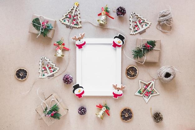 Marco de fotos entre adornos navideños y cajas de regalo.