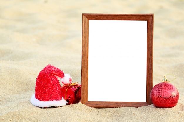 Marco de fotos con adornos navideños en la playa.