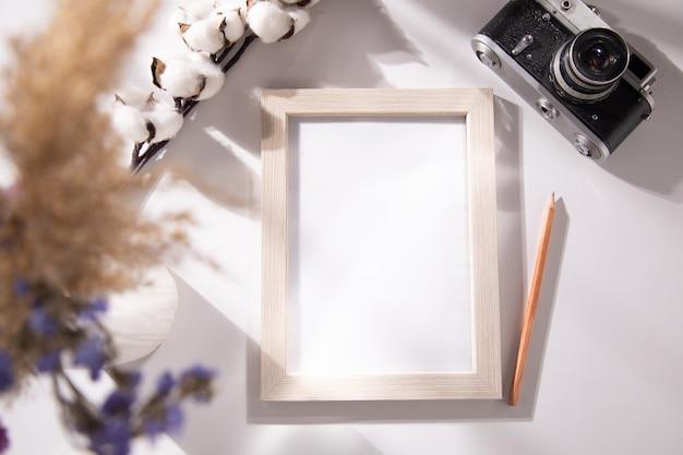 Marco de fotos con algodón y cámara en mesa
