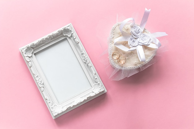 Marco de fotos y anillos de oro en ataúd blanco para aniversario de matrimonio sobre fondo rosa. concepto de amor