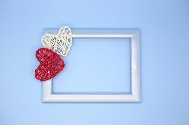 Marco de fotos azul sobre un fondo azul con corazones de madera roja y blanca