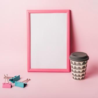 Marco de fotos blanco con borde; clips de papel y taza desechable de café sobre fondo rosa