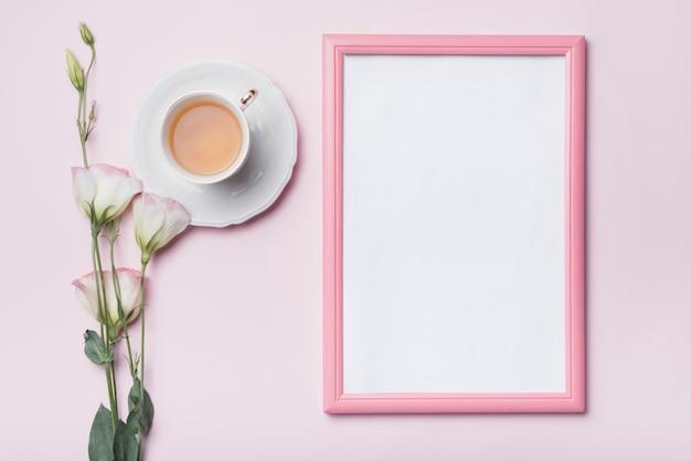 Marco de fotos en blanco con borde rosa; taza de té y flores frescas de eustoma contra el fondo coloreado