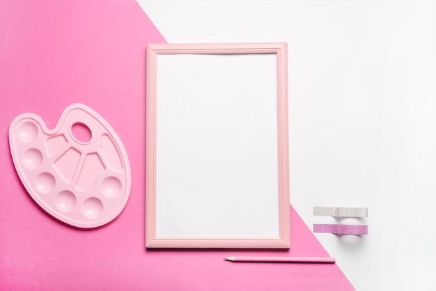 Marco de fotos blanco con cintas; lápiz y paleta en doble fondo.