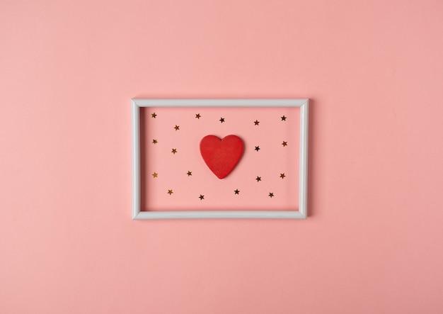 Marco de fotos blanco con corazón rojo y estrellas doradas en el interior sobre fondo rosa. concepto de san valentín. vista plana endecha, superior.