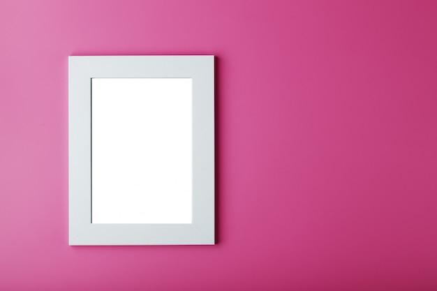 Marco de fotos blanco con un espacio vacío sobre un fondo rosa.