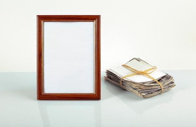 Marco de fotos en blanco para fotos, flor en una maceta, pila de fotos antiguas sobre la mesa.