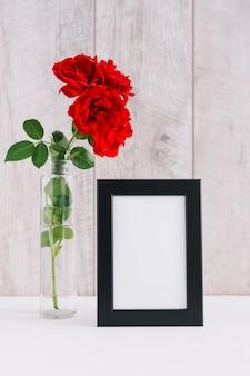 Marco de fotos en blanco y hermosas flores rojas en florero