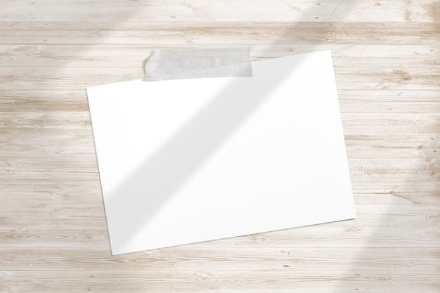 Marco de fotos en blanco pegado con cinta adhesiva a madera con textura con suaves sombras de ventana de adobe
