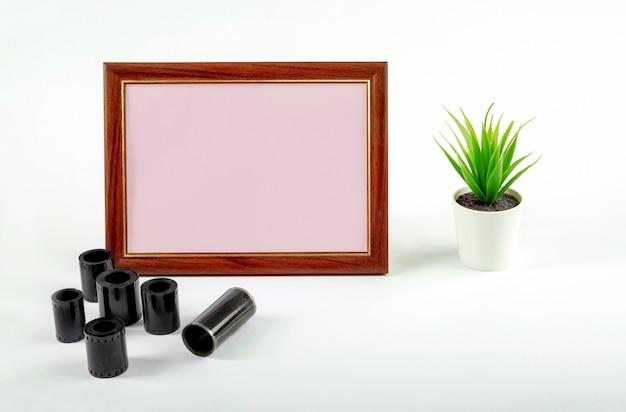Marco de fotos en blanco, película fotográfica sobre la mesa. maquillaje.