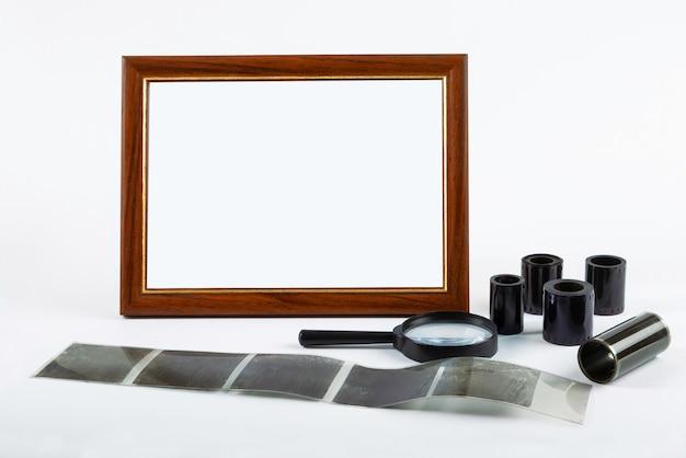 Marco de fotos en blanco, película fotográfica sobre la mesa.