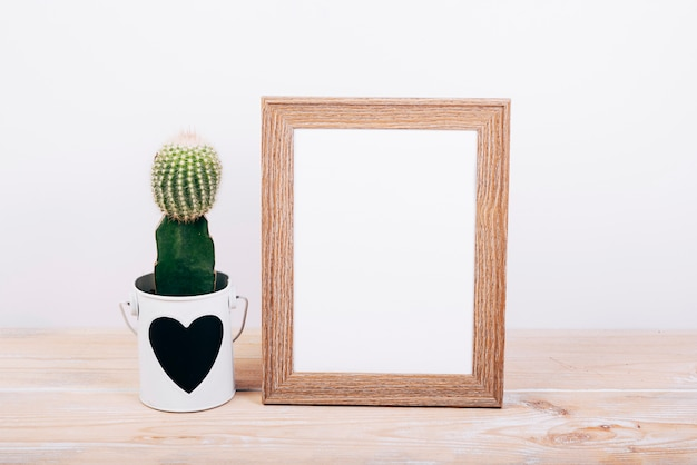Marco de fotos en blanco y planta suculenta con heartshape en maceta sobre mesa de madera