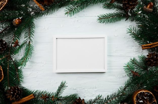 Marco de fotos blanco entre ramas de abeto