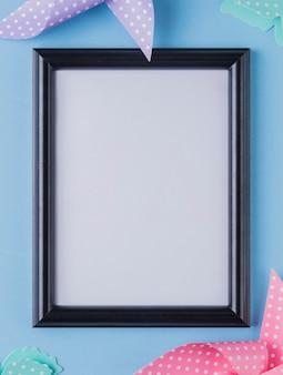 Marco de fotos en blanco rodeado de papel de origami