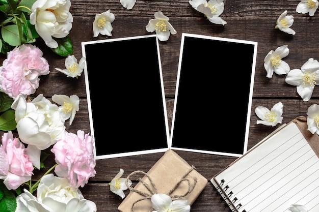 Marco de fotos en blanco con rosas y flores de jazmín, caja de regalo y cuaderno forrado