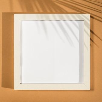 Marco de fotos blanco sobre un fondo beige con una sombra de hoja de palma