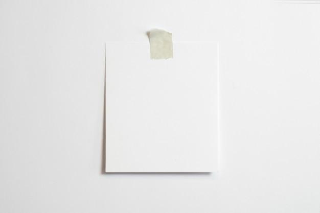 Marco de fotos en blanco con sombras suaves y cinta adhesiva aislado sobre fondo de papel blanco
