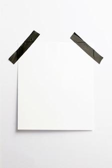 Marco de fotos en blanco con sombras suaves y cinta adhesiva negra aislada sobre fondo de papel blanco