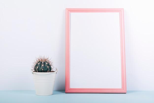 Marco de fotos en blanco con una suculenta pequeña planta en maceta en mesa azul