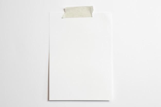 Marco de fotos en blanco de tamaño 10 x 15 con sombras suaves y cinta adhesiva aislada sobre fondo de papel blanco