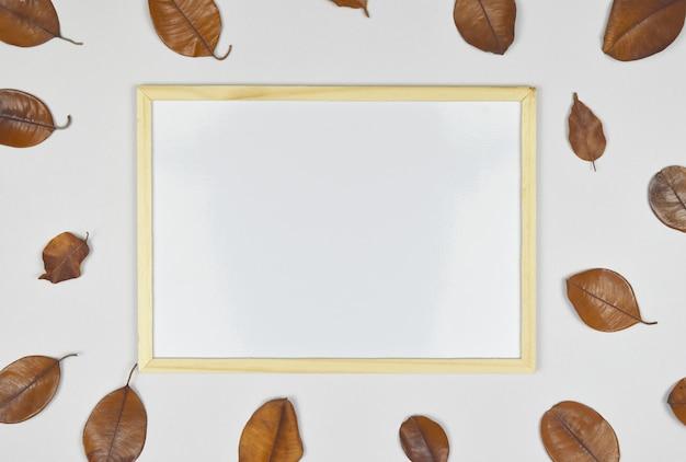 Marco de fotos en blanco vacío con hoja seca en el lado.