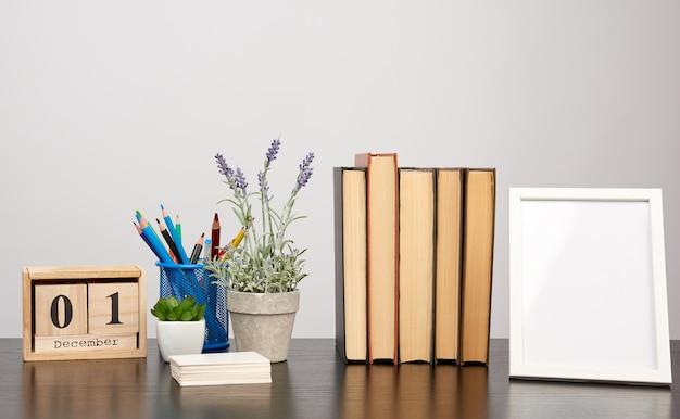 Marco de fotos blanco vacío, pila de libros y una maceta de lavanda en crecimiento sobre una mesa negra
