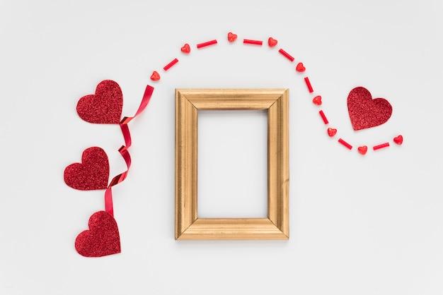 Marco de fotos cerca de adorno corazones y banda