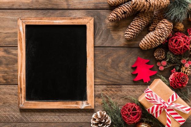 Marco de fotos cerca de caja de regalo, ramas de abeto, enganches de adorno y bolas de navidad