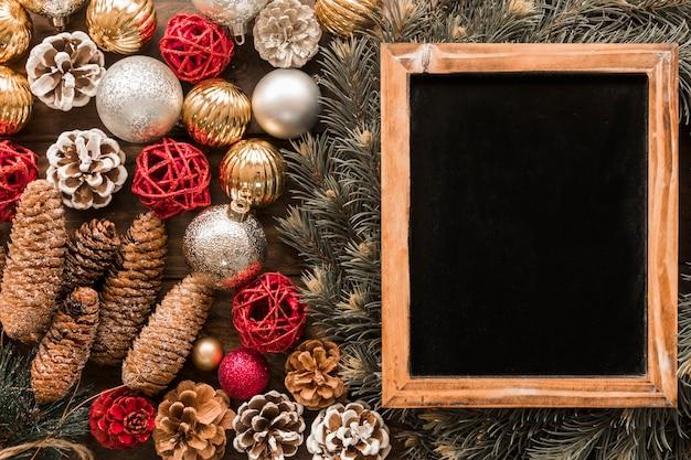 Marco de fotos cerca de ramas de abeto y juguetes navideños.