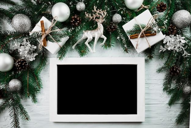 Marco de fotos cerca de ramitas de navidad
