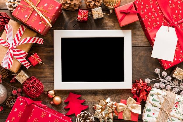 Marco de fotos cerca de set de cajas de regalo y adornos navideños.