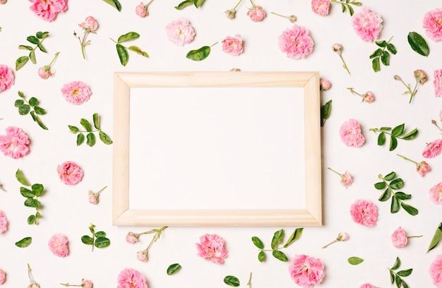 Marco de fotos entre colección de flores rosas y hojas verdes.