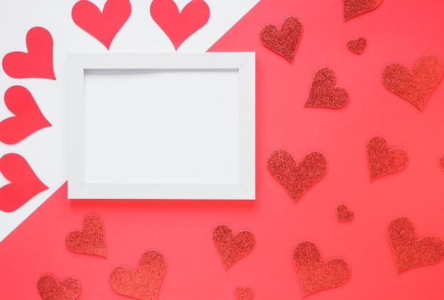 Marco de fotos entre conjunto de corazones de papel.